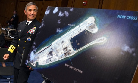 Adm. Harry Harris, commander of U.S. Pacific Command, walks past a photograph showing an artificial island China has built on the Fiery Cross Reef before an October 2015 congressional hearing.