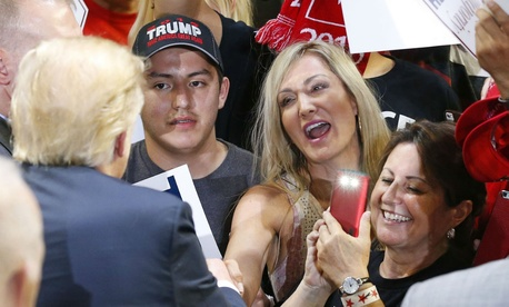Republican presidential candidate Donald Trump signs autographs for supporters after speaking at a rally in Phoenix.