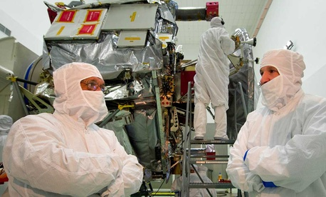 NASA Administrator Charles Bolden, left, listens to Juno program manager for Lockheed Martin Space Systems Company Tim Gasparrini as they view the Jupiter-bound Juno spacecraft in 2011