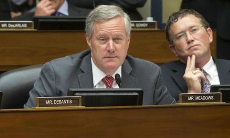 Reps. Mark Meadows, R-N.C., (center) and Thomas Massie, R-Ky., listen as Comey testifies.