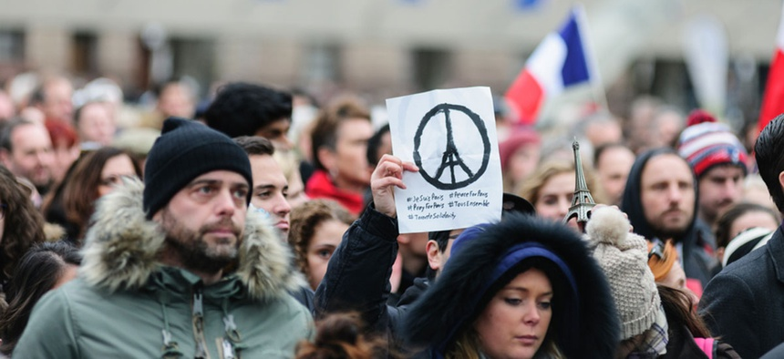 Crowds gather at Toronto's Nathan Phillips Square for a silent vigil for the 2015 Paris attacks.