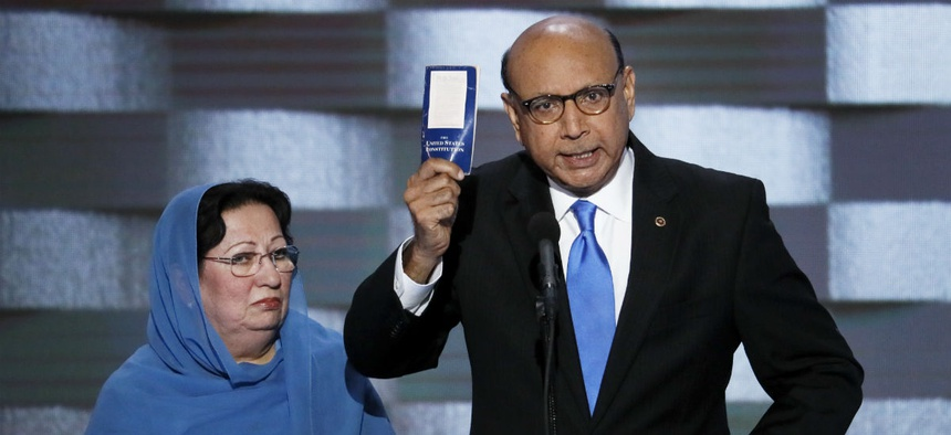 Khizr Khan, father of fallen U.S. Army Capt. Humayun S. M. Khan, holds up a copy of the Constitution as his wife, Ghazala, listens during the Democratic National Convention.