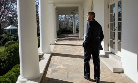 President Obama looks out over the Rose Garden as he walks along the Colonnade of the White House.