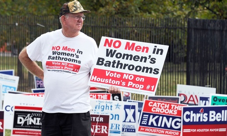 A demonstrator holds a sign against the Houston Equal Rights Ordinance outside an early voting center in Houston in 2015.