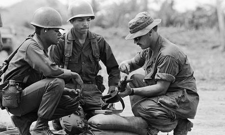 A U.S. military advisor instructs Honduran troopers in Puerto Castilla, Honduras, in 1983.
