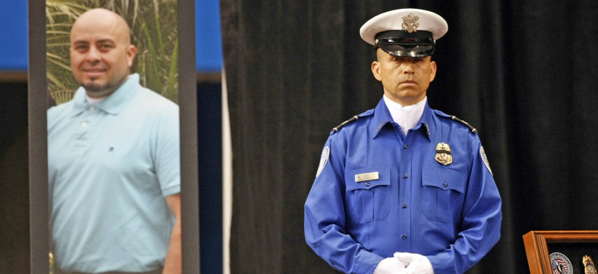 A Transportation Security Administration officer stands in front of a portrait of slain TSA officer Gerardo Hernandez during his public memorial at the Los Angeles Sports Arena in 2013.