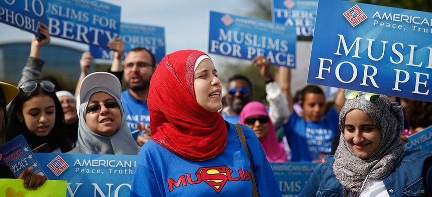 """Protesters stand across the street from a Donald Trump rally holding signs for """"Muslims for Peace"""" in Orlando in February."""