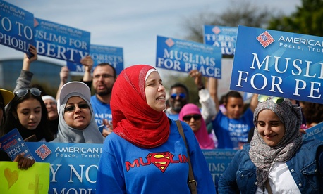 "Protesters stand across the street from a Donald Trump rally holding signs for ""Muslims for Peace"" in Orlando in February."