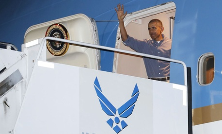 Obama waves as he arrives on Air Force One for his annual family vacation in Hawaii. Trump has targeted a contract to modernize Air Force One.