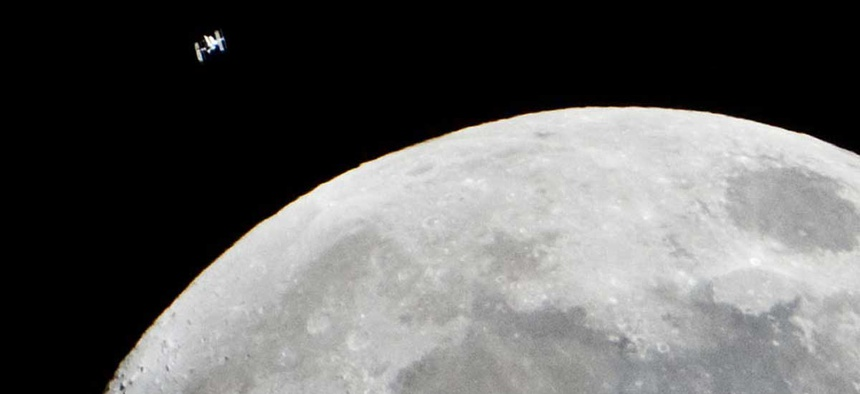 The International Space Station passes by the moon in 2015.