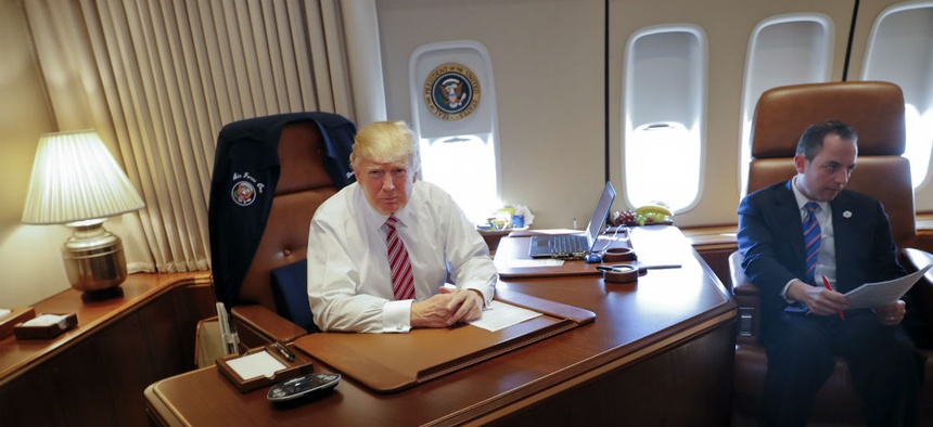 President Donald Trump, with his Chief of Staff Reince Priebus, sits at his desk on Air Force One on Thursday.
