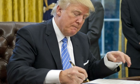 President Trump signs orders including the hiring freeze on Monday.