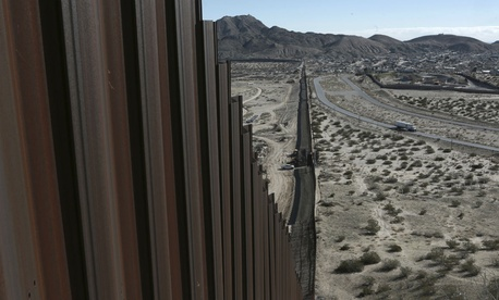 A truck drives near the Mexico-US border fence, on the Mexican side, separating the towns of Anapra, Mexico and Sunland Park, New Mexico, in January.