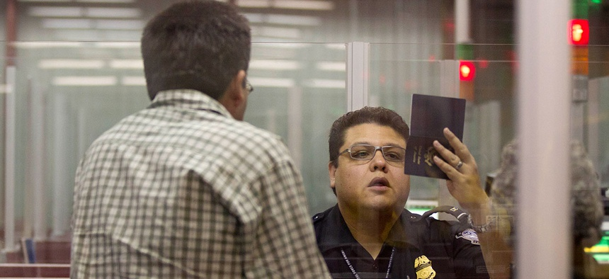 A Customs and Border Protection officer checks a passport inside immigration control at McCarran International Airport in 2011.