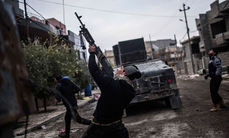A member of the Iraqi Special Forces shoots his machine gun at an Islamic State militant drone n the al-Barid district in Mosul, Iraq on Dec. 18, 2016.