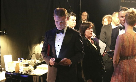 PricewaterhouseCoopers accountant Brian Cullinan, center, holds red envelopes under his arm while using his cell phone backstage at the Oscars.