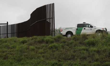 In this Nov. 13, 2016, photo, a U.S. Customs and Border Patrol agent passes along a section of border wall in Hidalgo, Texas.
