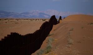 A CBP vehicle drives along the U.S.-Mexico border fence near Yuma, Arizona in 2010.