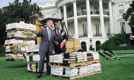 Bill Clinton gestures as he and Al Gore stand by a forklift with reams of federal bureaucratic rules and regulations outside the White House in 1993.