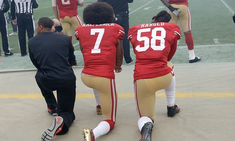 Colin Kaepernick and teammate Eli Harold kneel in December