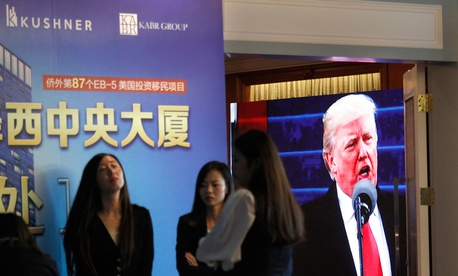 projector screen shows a footage of U.S. President Donald Trump as workers wait for investors at a reception desk during an event promoting EB-5 investment in a Kushner Companies development at a hotel in Shanghai, China, Sunday, May 7, 2017.