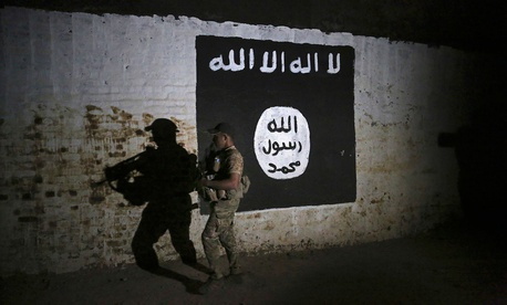 An Iraqi soldier inspects a recently-discovered train tunnel, adorned with an Islamic State group flag in March.