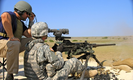 A technical trainer for CACI Inc. provides guidance to a solider from the 41st Fires Brigade, during a familiarization fire with the PAS-13 sight at Fort Hood, Texas in 2013.