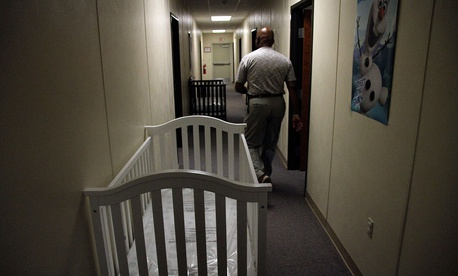 A federal employee walks past cribs inside of the barracks for law enforcement trainees turned into immigrant detention center at the Federal Law Enforcement Center (FLETC) in Artesia, N.M. in 2014.