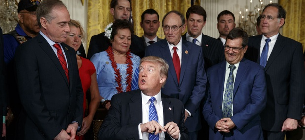 President Trump speaks to VA Secretary David Shulkin before signing the reform bill into law.