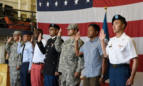 Service members recite the oath of allegiance during a naturalization ceremony conducted in the hanger bay on board USS Somerset in Seattle in 2016.