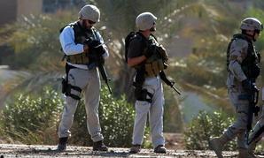 Two U.S. private security contractors investigate a site in Iraq in 2004.