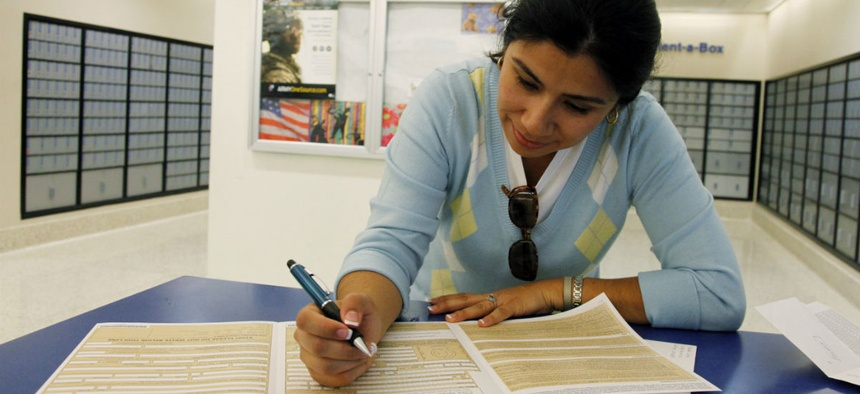 A passport applicant fills out forms in Los Angeles. Applications have spiked recently, requiring an increase in mandatory overtime at some State Department offices.
