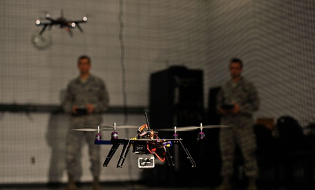 Air Force Capt. Wilfred Noel, deputy chief of the Air Force Research Lab, left, and 1st Lt. Jason Rathje, an advanced weapon design engineer with Air Force Research Lab weapons dynamics and control science branch, right, pilot quadrotor vehicles.