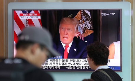 People walk by a TV screen showing a local news program reporting with an image of U.S. President Donald Trump at the Seoul Train Station Wednesday.
