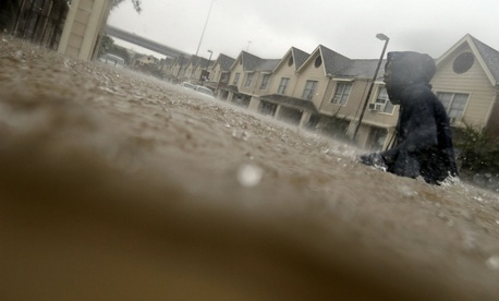 A child makes his way through floodwaters from Tropical Storm Harvey in Houston on Aug. 27, 2017.