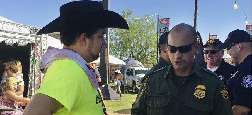 A U.S. Border Patrol agent gives information about working for the agency to Ric Kindle in April, at the Country Thunder Music Festival in Florence, Ariz.