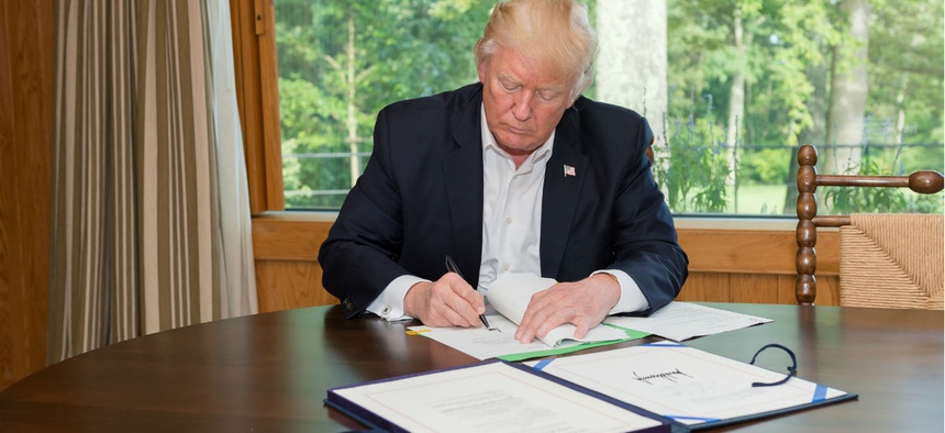 President Donald Trump signs the Hurricane Harvey Funding Bill.