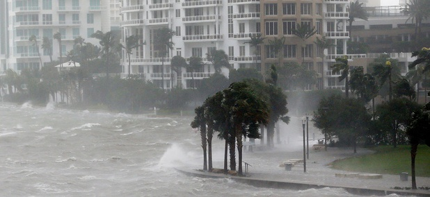 Waves crash over a seawall at the mouth of the Miami River from Biscayne Bay on Sunday.