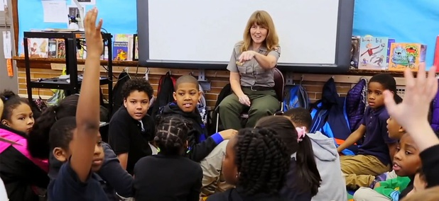 A screenshot from the ad shows a federal employee speaking to children.
