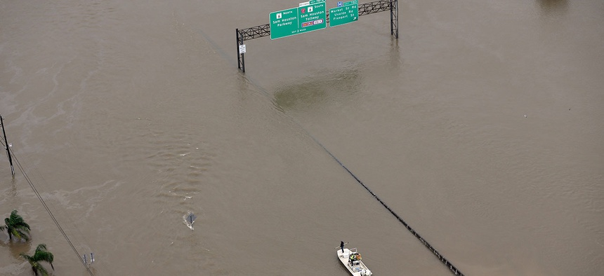 A boat travels along Interstate 10 as floodwaters from Tropical Storm Harvey cover a portion of the highway in August.