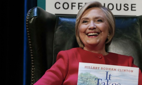 "Former Democratic presidential candidate and Secretary of State Hillary Clinton sits on stage at the Warner Theatre in Washington during a stop on a tour for her latest book, ""What Happened."""