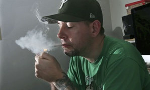 In this March 10, 2016, photo, former U.S. Marine, Mike Whiter lights a marijuana cigarette at his home in Philadelphia. Some veterans say marijuana helps them manage their anxiety, insomnia and nightmares.