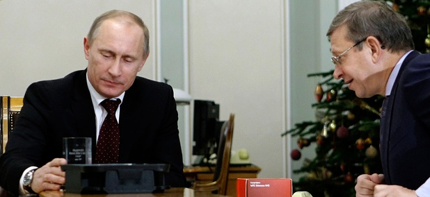 Russian Prime Minister Vladimir Putin, left, holds a computer chip and a cell phone programmed to receive signals from Glonass in 2010.