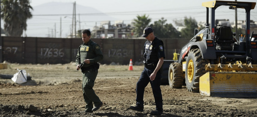A Border Patrol agent walks with a Homeland Security official as crews work on prototypes for President Trump's proposed border wall.