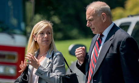 White House Chief of Staff John Kelly and Deputy Chief of Staff Kirstjen Nielsen speak together as they walk across the South Lawn of the White House in Washington.