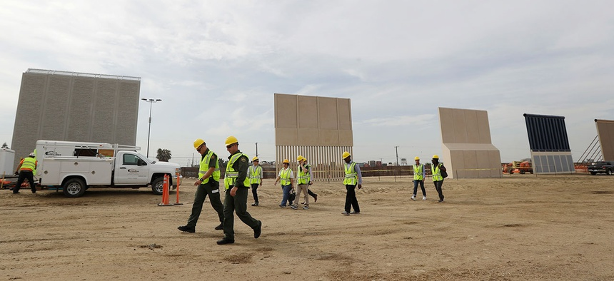 People pass border wall prototypes as they stand near San Diego on Oct. 19.