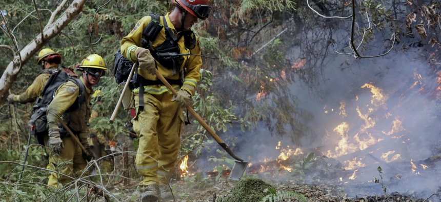 Fire crews build a containment line in mid-October as they battle a wildfire near Boulder Creek, Calif.