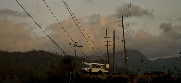 A repair team works on power lines on Oct. 14. A month after Hurricane Maria struck Puerto Rico, power is still out for the vast majority of people.