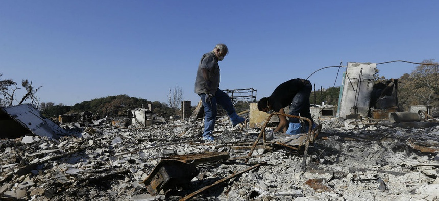 Friends search through the remains of a home destroyed in Santa Rosa, California, wildfires.