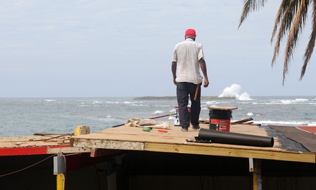 Manuel Dia repairs the roof of a restaurant in Carolina, Puerto Rico on Nov. 20.